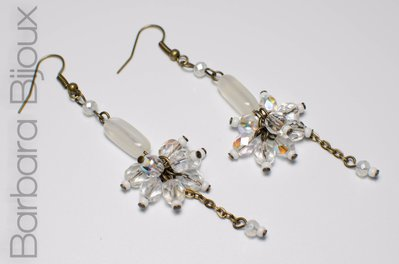 Orecchini pendenti con perle di vetro sul bianco trasparente.
