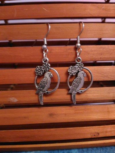 Orecchini pendenti cerchio in metallo con pappagallo su trespolo e fiori