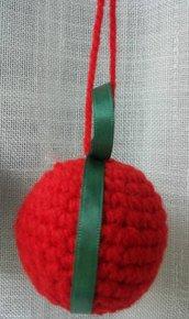 Palla di Natale rossa in lana tecnica amigurumi con rifinitura in nastro seta verde