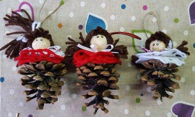 Tre bambolina natalizie con pigna