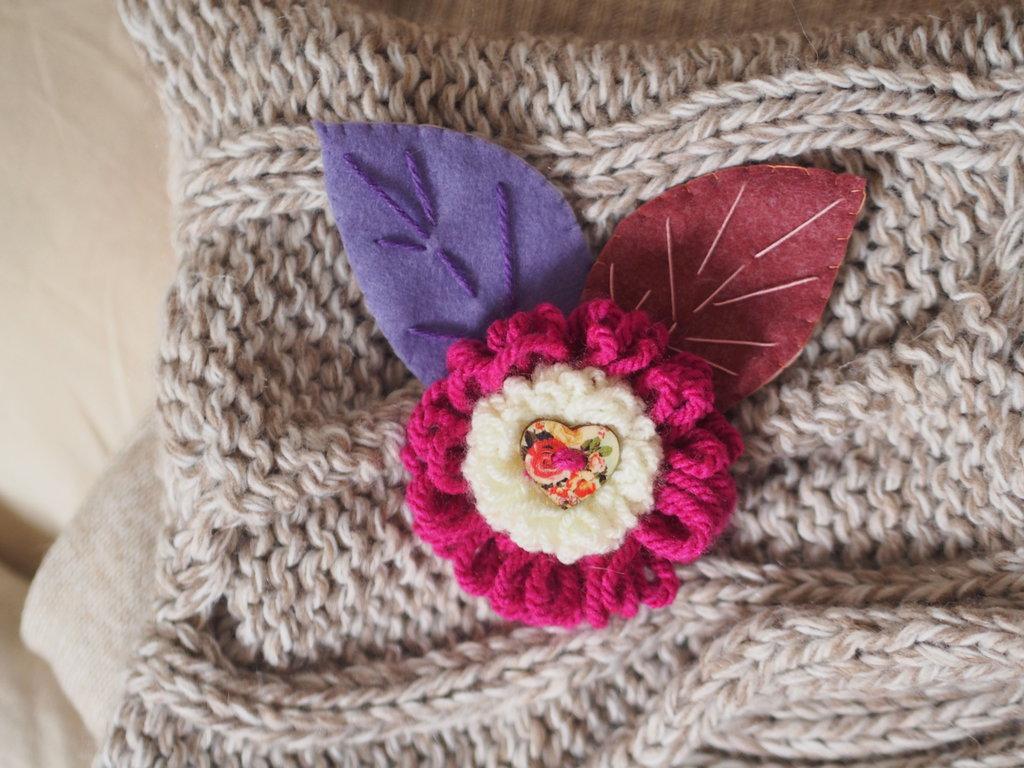 SPILLA in lana e feltro.Due fiori sovrapposti lavorati a telaio,foglie in feltro ricamate.Bottone a cuore in legno dipinto.Fuchsia,ciclamino e lilla.