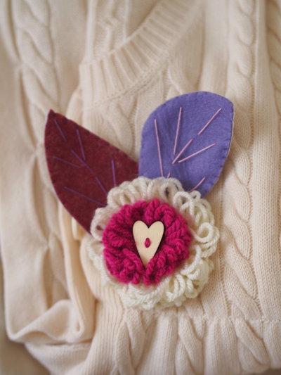 SPILLA in lana e feltro.Due fiori sovrapposti lavorati a telaio,foglie in feltro ricamate.Bottone a cuore in legno.Fuchsia,ciclamino e lilla.