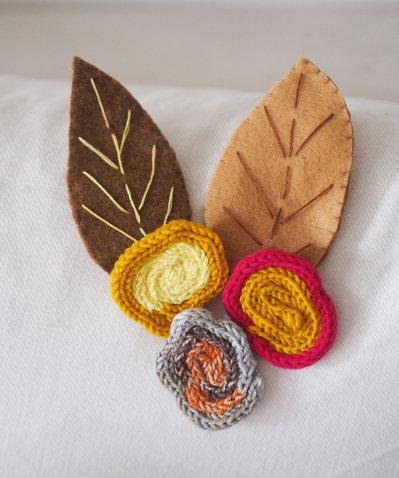 SPILLA in lana e feltro.Rose in maglia tubolare e foglie ricamate in feltro.Foglie sui toni del bruciato.Fiori toni gialli.Accessorio,gioiello-DONNA