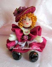 Bambolina in pasta di mais, vestitino e cappellino in raso color magenta