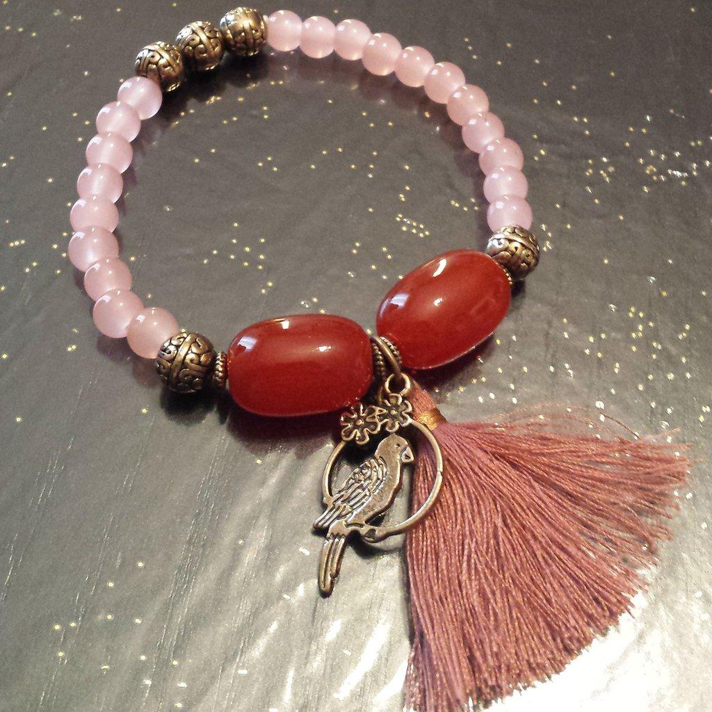 Bracciale elastico perline rosa, nappina rosa cipria e ciondolo uccellino
