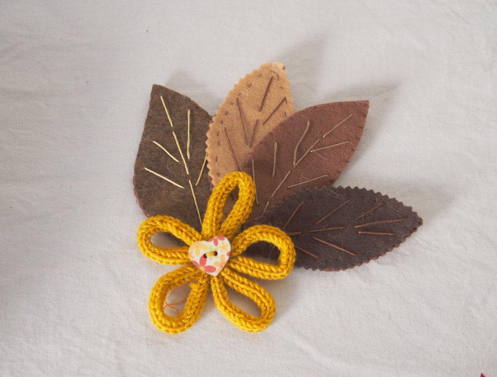 SPILLA in lana e feltro(toni marrone).4foglie ricamate,fiore in lana tubolare.Bottone in legno dipinto.Gioiello,accessorio donna.Bomboniera.REGALO NATALE