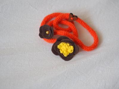BRACCIALE arancione zucca in lana tubolare.Tre fili.Applicazione di fiori in feltro marrone e giallo.Bottone a cuore in legno,perla.Accessorio,gioiello invernale.