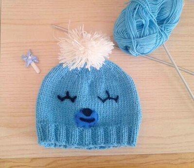 Cappello pon-pon neonato in lana merinos ai ferri