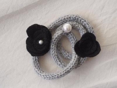 BRACCIALE grigio perla in lana tubolare.Tre fili.Applicazione di 2 rose in feltro nero.Perla gigante e perla piccola.Accessorio,gioiello invernale.