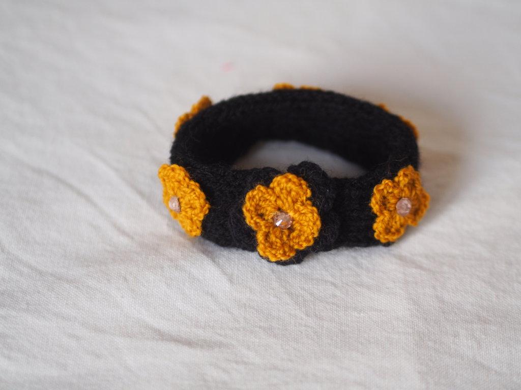 BRACCIALE,fascia in maglia di lana nera con aggiunta di 6 margherite senape all'uncinetto,una margherita nera e strass rosati.Accessorio,gioiello  primaverile