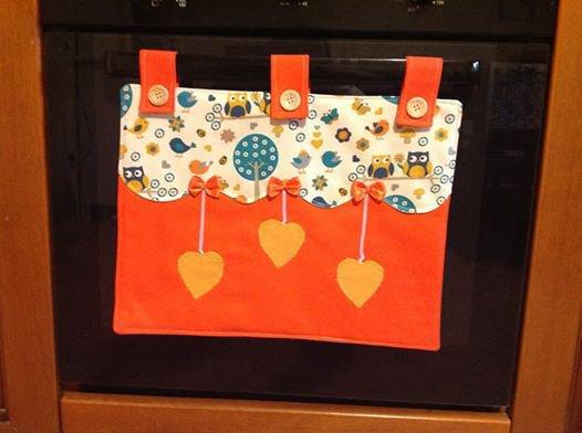 copri forno arancione con gufi e cuori gialli.