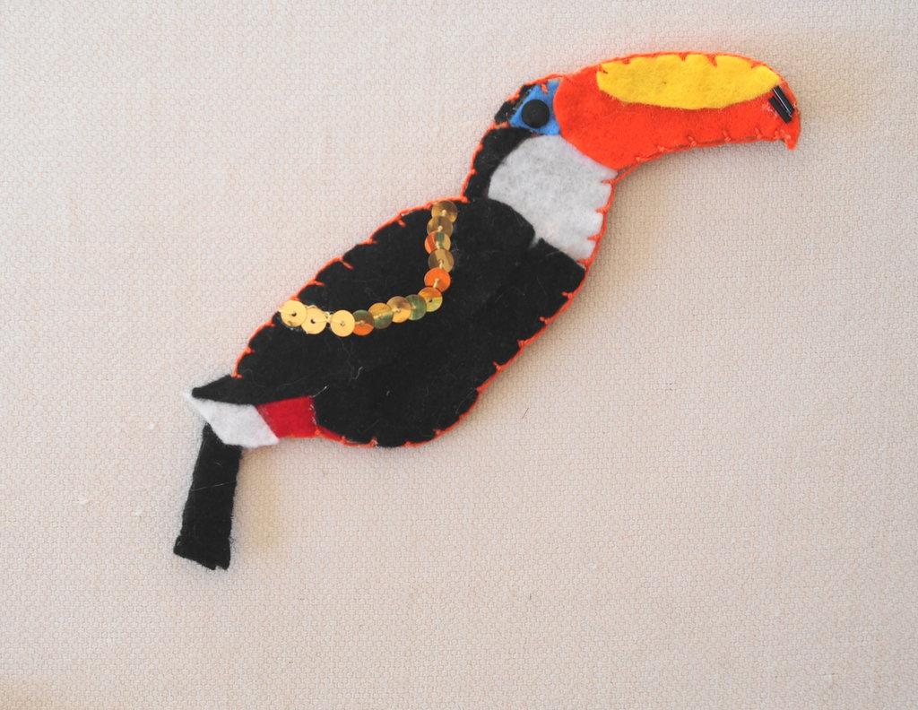SPILLA in FELTRO,sapore TROPICALE.Tucano.Dettagli curati.Feltro nero,bianco,arancione,giallo.Arricchita da paillettes/perline.Accessorio donna,gioiello originale.