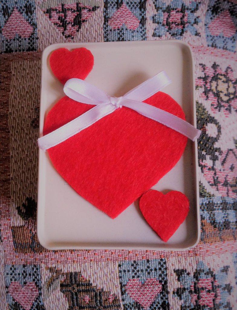 scatolina regalo San Valentino in latta color crema double-face contenente una spilla con un fiore rosso e e due mollettine con cuoricini rossi