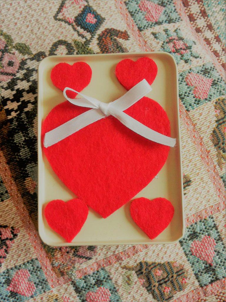 scatolina regalo San Valentino in latta color crema double-face contenente un cuore color ambra trasparente con tre roselline applicate sopra un braccialetto rigido glitterato color orasoprae due mollettine con cuoricini rossi