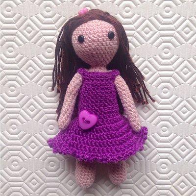 Bambolina amigurumi con i capelli lunghi e vestitino viola, fatta a mano all'uncinetto