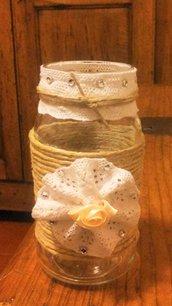 Barattottolo in vetro di forma allungata decorato con spago fine marrone con coccarda in trina ad uncinetto bianca rosellina centrale impreziosito da piccoli strass