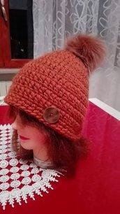 Cappello con pon pon di volpe lavorato all'uncinetto.