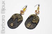 Orecchini pendenti ovali colore nero con texture e decorazione colore oro.
