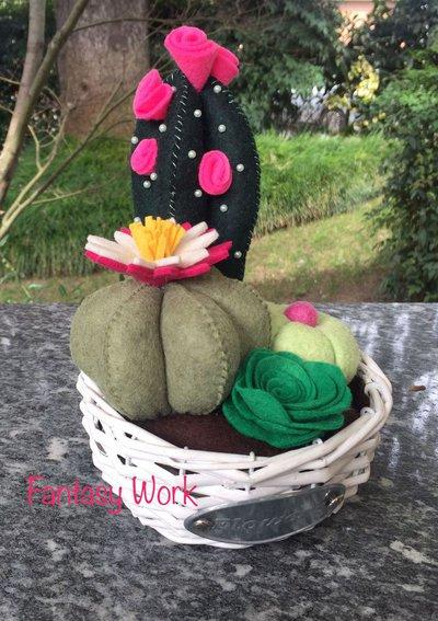 Composizione di cactus di feltro in cestino di vimini rotondo, con fiori di feltro rosa e fucsia