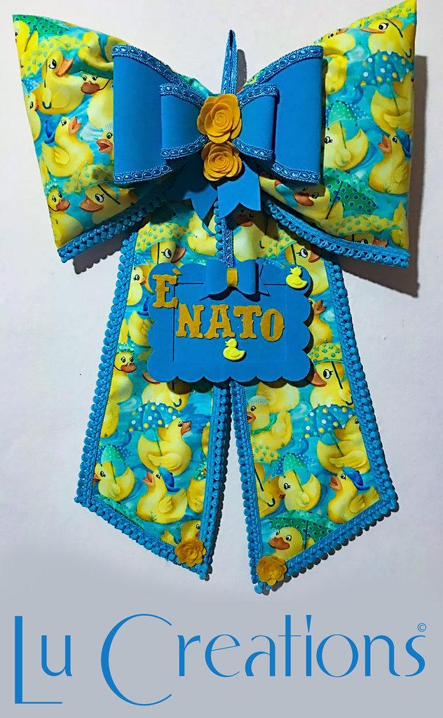 Fiocco nascita azzurro con paperelle e roselline gialle.