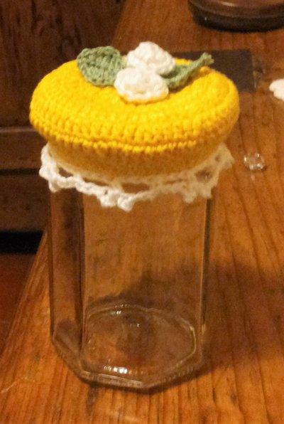 copri barattolo lavorato ad uncinetto con filato cotone giallo e decorato con roselline bianche con foglioline e bordo rifinitura bianco