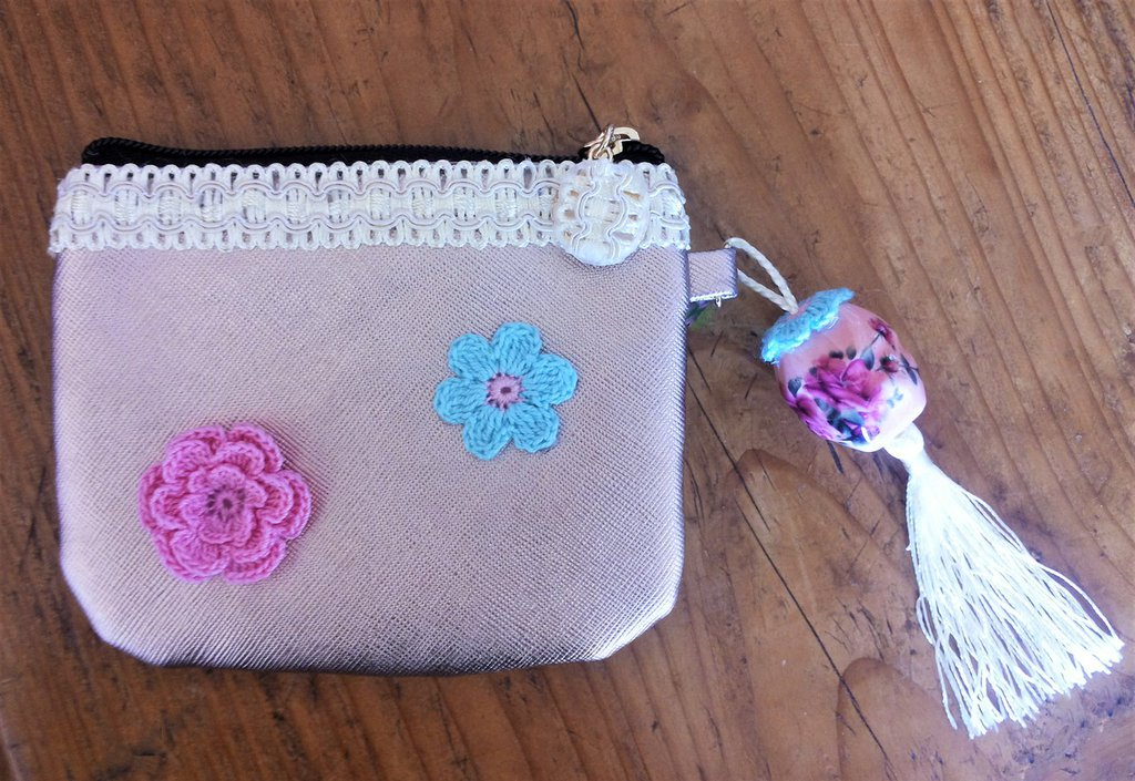 Piccola pochette in pelle dorata sfumata sul rosa decorata con passamaneria e roselline e fiori ad uncinetto sia sul fronte che sul retro