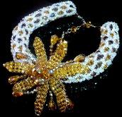 Collana tubolare in cristallo con fiori centrali a intreccio, regolabile.