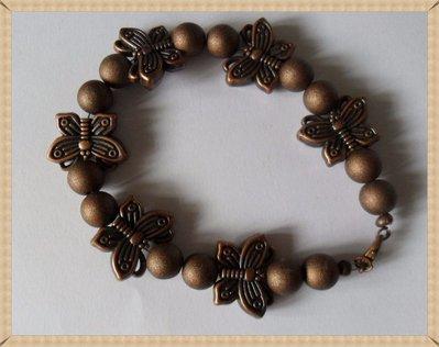 Cavigliera di perle marroni metallizzate e farfalle