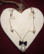 Collana con pendente perla a goccia e fiocco blu.