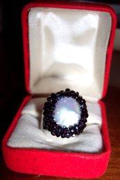Anello con perla barocca piatta incastonato con rondelle cinesi blu.