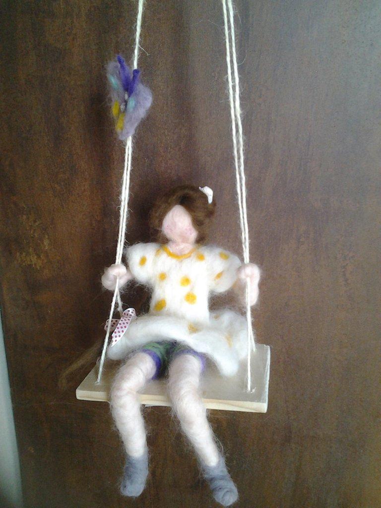 Bambola sull'altalena in lana cardata