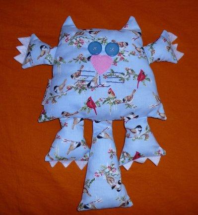 Pupazzo a forma di gatto azzurro con uccellini