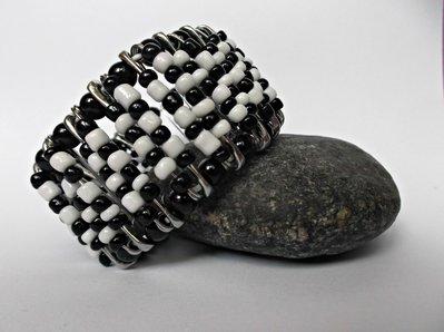 Bracciale elastico nero e bianco con spille da balia e perline colorate
