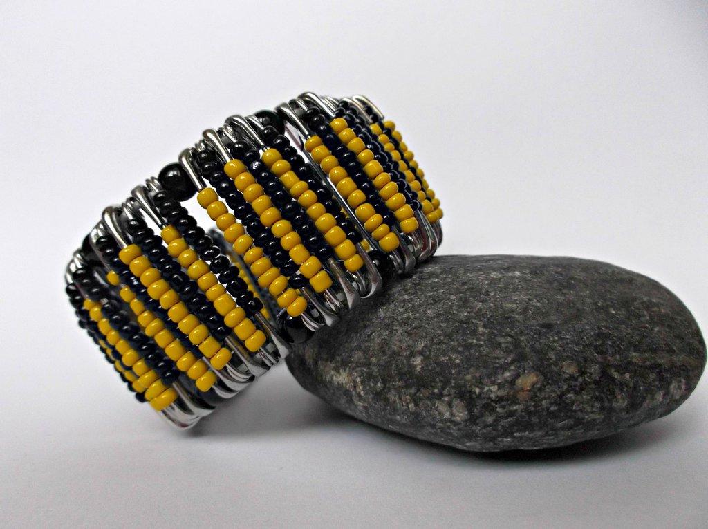 Bracciale elastico giallo e nero con spille da balia e perline colorate