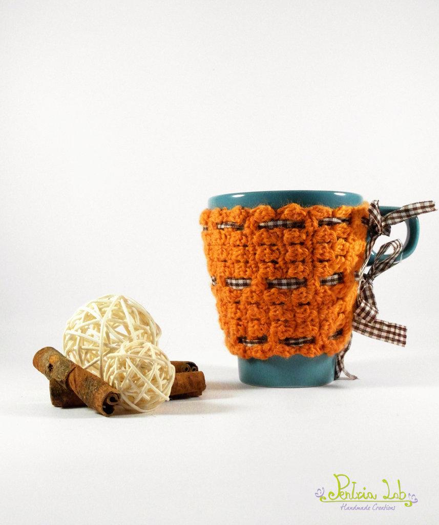 copri tazza fatto ad uncinetto di colore arancio con nastrino a quadretti bianco e marrone , tazza color turchese