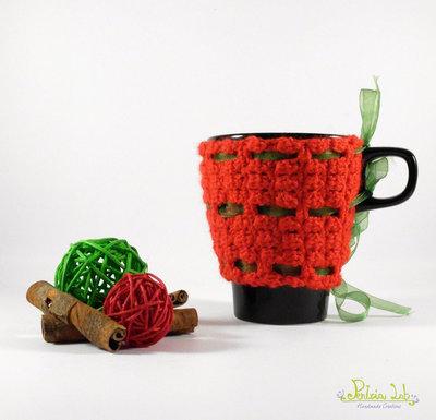 copri tazza colore rosso fatto ad uncinetto con nastrino organza verde , tazza nera