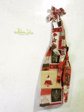 Grembiule realizzato con tessuto a fantasia natalizia con babbi natale, casette di marzapane e bastoncini di zucchero e tasca