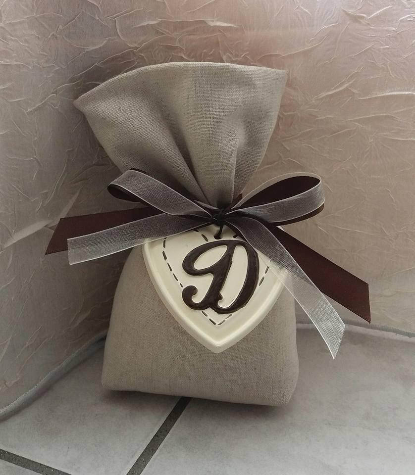 Sacchetto bomboniera in lino con cuore ed iniziale in gesso ceramico dipinto a mano