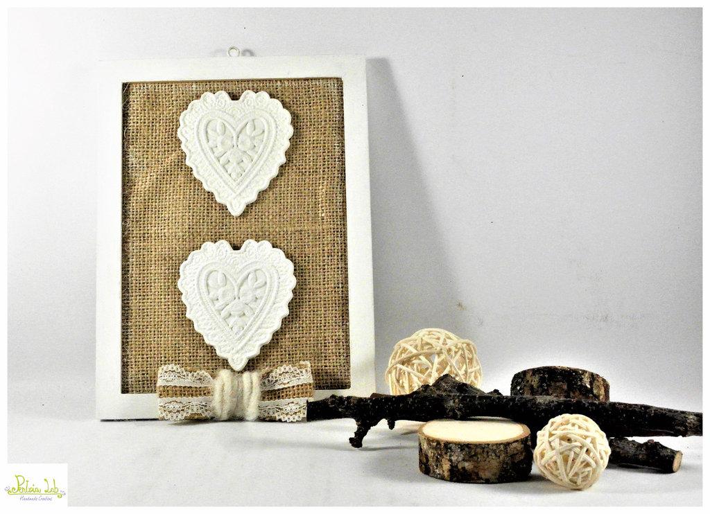 Quadretto decorativo con cuori di gesso ceramico bianco su fondo in tessuto di juta.