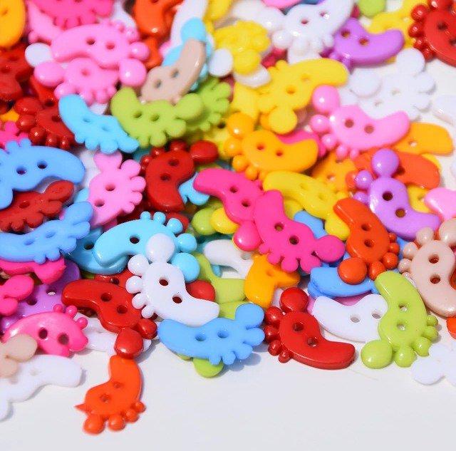 10 bottoni in plastica a forma di piedini