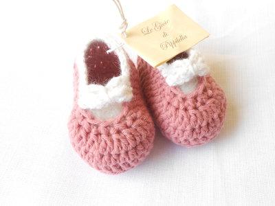 Scarpine crochet ballerine in lana rosa, con fiocco bianco.