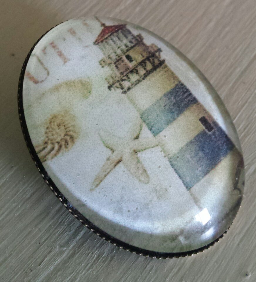 Spilla con cabochon in vetro ovale con faro e conchiglie