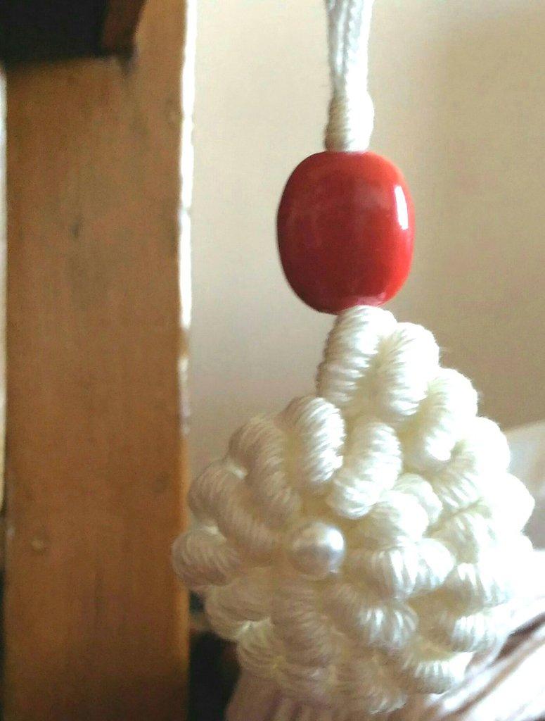 Ciondolo tessile conchiglione bianco in cotone realizzato ad uncinetto con punto molto decorativo ed impreziosito con corallo rosso in ceramica