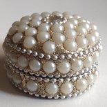 Bombiera di perle bianche illuminate da un sottofondo d'argento