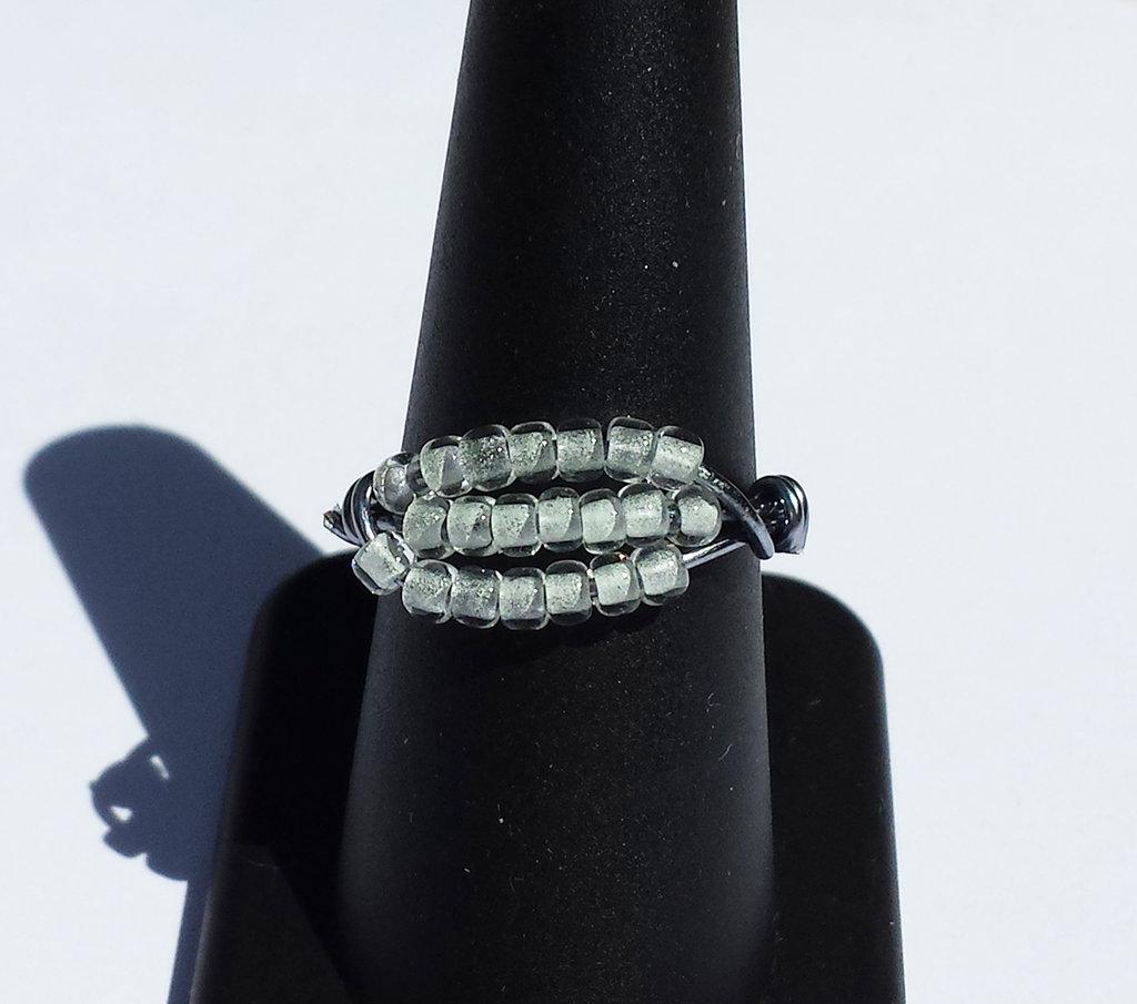 Anello con perline bianche che si illuminano al buio di blu chiaro