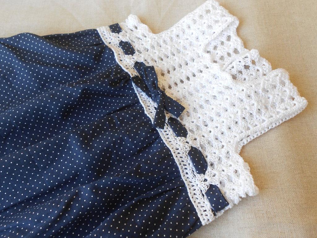 Vestitino prendisole con sprone crochet bianco e corpino con fiocco blu con poins bianchi.
