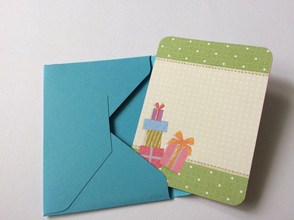 Biglietto auguri buon compleanno con pacchetti regalo e busta abbinata