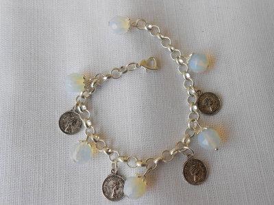 Bracciale con sfere sfaccettate di pietra dura e charms a forma di monete.