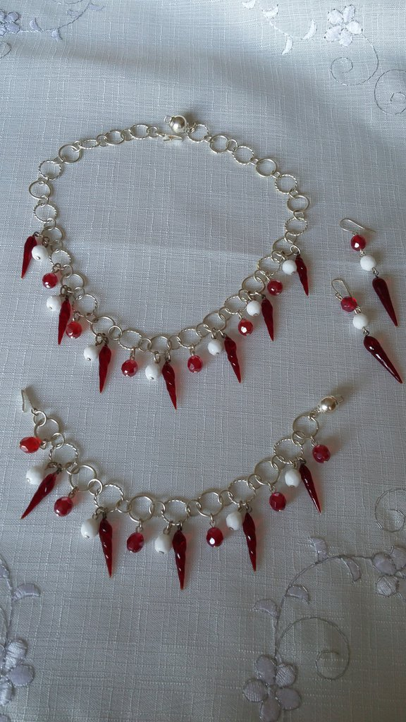 parure collana ,orecchini e bracciale con catena in argento indiano, mezzo cristallo rosso e bianco e cornetti in  vetro di murano rosso