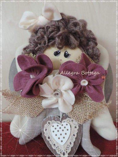 Bambola con i fiori su cuore di  legno